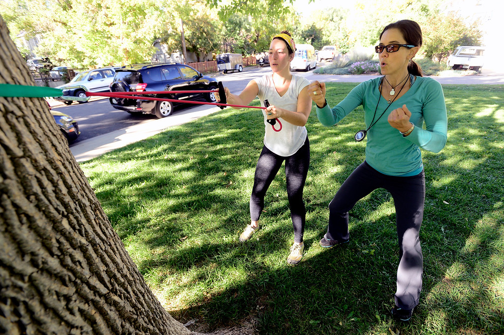 . Avery Oatman, left, gets encouragement in an arm exercise from instructor Annette Bray during their ski conditioning class in North Boulder Park on Wednesday, Oct 2, 2013. For more photos and a video of the class go to www.dailycamera.com Paul Aiken / Camera