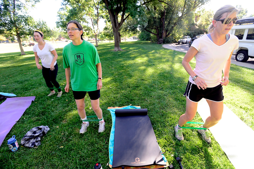 . From left to right Avery Oatman, Kate Kelsch and Lisa Shoemaker use resistance bands during a leg exercise during instructor Annette Bray\'s ski conditioning class in North Boulder Park on Wednesday, Oct 2, 2013. For more photos and a video of the class go to www.dailycamera.com Paul Aiken / Camera