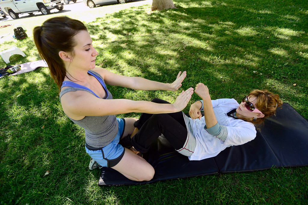 . Dawn Korres punches Brooke Null\'s hands during a abdominal exercise in instructor Annette Bray\'s ski conditioning class in North Boulder Park on Wednesday, Oct 2, 2013. For more photos and a video of the class go to www.dailycamera.com Paul Aiken / Camera