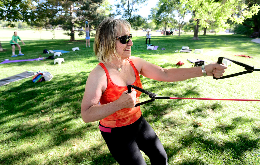 . Pat Lehman works a pulling arm exercise with resistance bands during instructor Annette Bray\'s ski conditioning class in North Boulder Park on Wednesday, Oct 2, 2013. For more photos and a video of the class go to www.dailycamera.com Paul Aiken / Camera