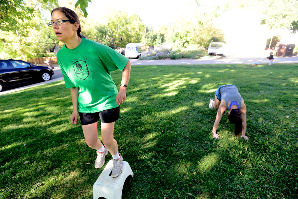 . Kate Kelsch does platform leg jumps while Brooke Null does mountain climbers during instructor Annette Bray\'s ski conditioning class in North Boulder Park on Wednesday, Oct 2, 2013. For more photos and a video of the class go to www.dailycamera.com Paul Aiken / Camera