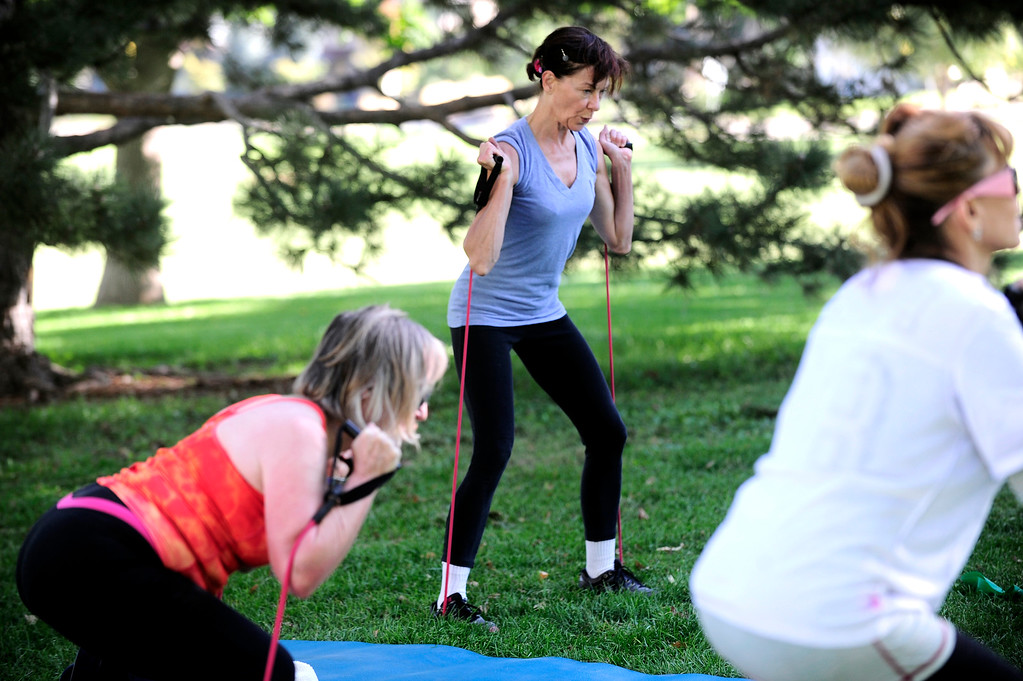 . Deb Marshall uses resistance bands during a squat leg exercise during instructor Annette Bray\'s ski conditioning class in North Boulder Park on Wednesday, Oct 2, 2013. For more photos and a video of the class go to www.dailycamera.com Paul Aiken / Camera