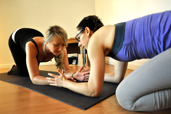 Andrea Flanagan, left, is guided by her instructor Ashley Quinn during a Spontaneous Yoga class held in Quinn's apartment in Boulder on Tuesday, September 4, 2012. Jessica Cuneo/ For the Daily Camera.