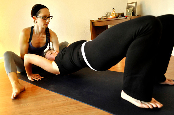Ashley Quinn, left, helps Andrea Flanagan into the Bridge position during a Spontaneous Yoga class held in Quinn's apartment in Boulder on Tuesday, September 4, 2012. Jessica Cuneo/ For the Daily Camera.