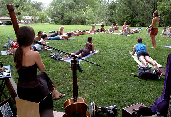 """Ariana Saraha, left,  provided the music for the yoga class.<br /> """"Yoga Rocks the Park"""" began in Boulder's Central Park on Sunday. The yoga and music gathering will continue every Sunday through September 19, 2010.<br /> For more photos and a video of yoga in the park, go to  <a href=""""http://www.dailycamera.com"""">http://www.dailycamera.com</a>.<br /> Cliff Grassmick / August 8, 2010"""