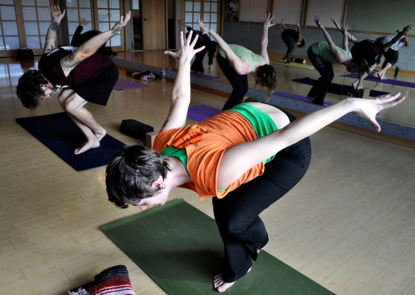 "Andrew Tompkins, left, and Elizabeth Banker, back right, follow their yoga instructor Melissa Carey, front, during a Yoga for Wellness class at Bodywork Bistro in Boulder on Monday Dec. 10, 2012. DAILY CAMERA/ JESSICA CUNEO. <br /> For video and a photo gallery go to  <a href=""http://www.dailycamera.com"">http://www.dailycamera.com</a>"