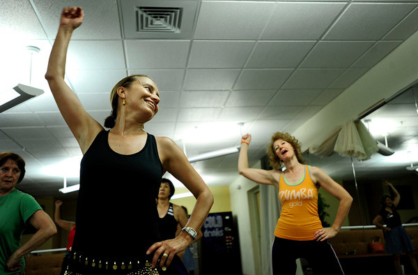 "From left, Desiree Fenichell, of Boulder, raises her arm during a workout  Tuesday morning with Assistant instructor Donna Shonle, of Boulder. Zumba Gold is a low impact version of Zumba but still maintains the basics of Zumba. July 3, 2012. Rachel Woolf/ For the Daily Camera. For more photos and a video of the workout, go to  <a href=""http://www.dailycamera.com"">http://www.dailycamera.com</a>."
