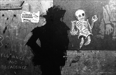 """Glorious Strangers"" - The shadow man graffiti - not sure of exact location - December, 1982. The shadow man was Richard Hambleton, whose graffiti art was all over the Lower east side, East village in the early 80's.  I shot about 10 frames of this specific work and liked this one the best - and it is the only Shadow man work I photographed. It was really the combination of the different works and tags that appealed to me.  I'm not sure of the specific location, but it was under some scaffolding .  Pretty sure it was in the East village."