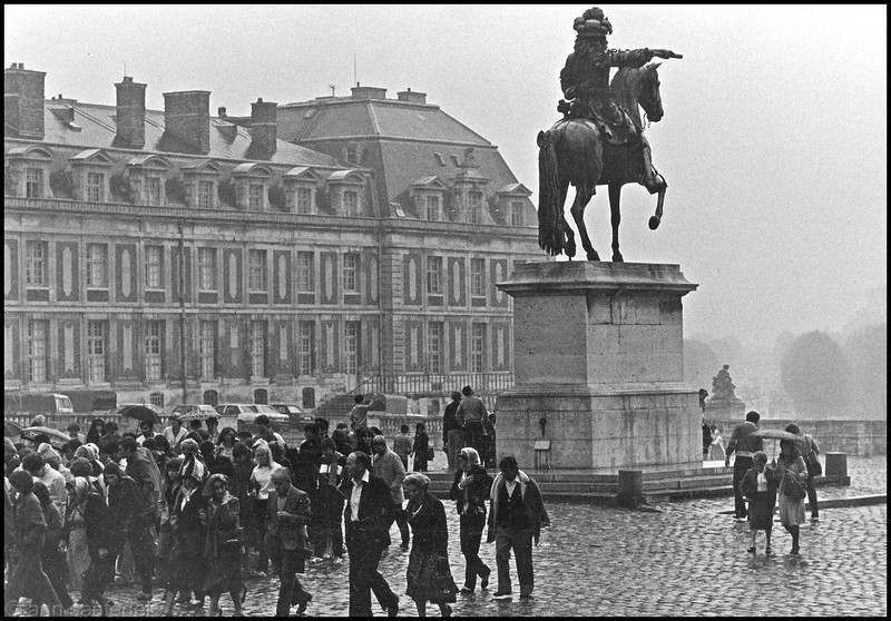 Vistors file past Statue of Louis XIV at Versailles