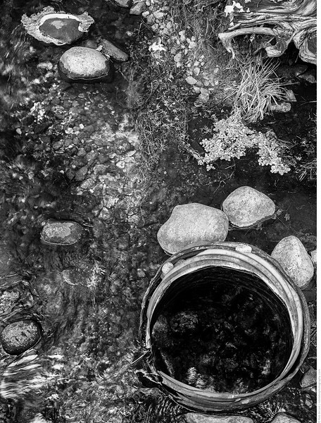 A culvert buried vertically in the creek bed fills with groundwater from the spring. People collect the spring water in jugs. An opening in the side of the culvert lets the spring water flow into the creek, where it supplies base flow and lowers the creek's water temperature.