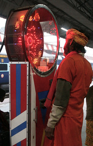 a sadhu at a fortune-telling scale in the train station