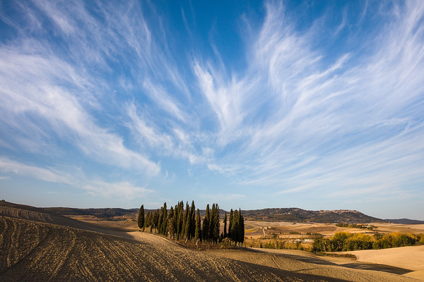 Clouds over cypress trees and Montalcino