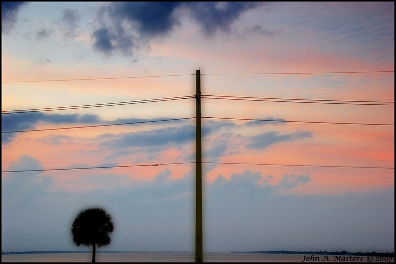 Sunset sky, power pole, and palm tree on the Eau Gallie Causeway, Melbourne, Florida.<br /> <br /> I used the Orton process on this shot.