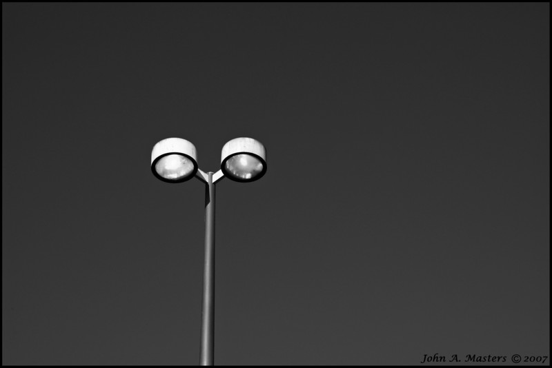 Black and white version of the parking lot lights at the Fee Avenue branch of the Brevard County Public Library in Melbourne, Florida.