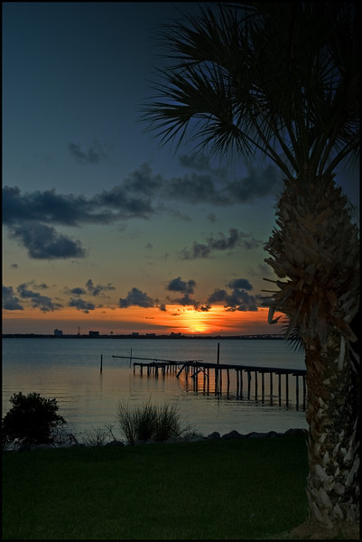 Sunset over the Indian River Lagoon and broken pier in Melbourne Beach, Florida.