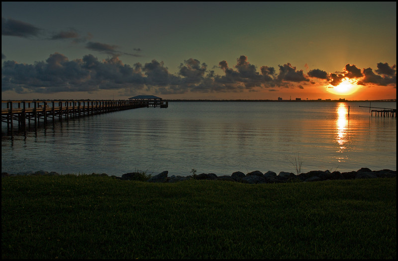 Sunset over the Indian River Lagoon and pier at Rykman Park in Melbourne Beach, Florida.
