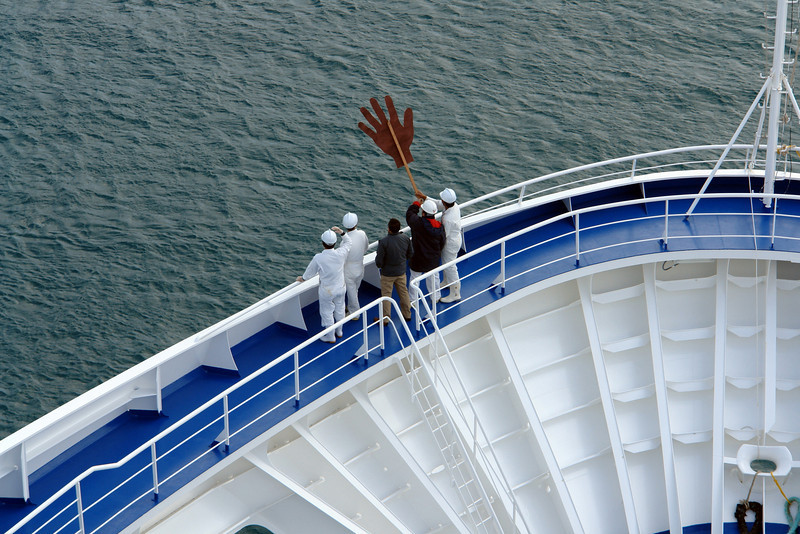 """Crew waving with their big hand to Regent's sister ship """"Seven Seas Mariner"""" that was also docked in Bermuda.  Our ship was the Voyager."""