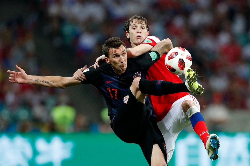 . Croatia\'s Mario Mandzukic, left, challenges for the ball with Russia\'s Mario Fernandes during the quarterfinal match between Russia and Croatia at the 2018 soccer World Cup in the Fisht Stadium, in Sochi, Russia, Saturday, July 7, 2018. (AP Photo/Rebecca Blackwell)
