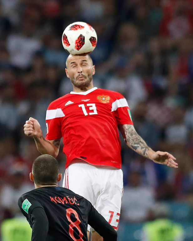 . Russia\'s Fyodor Kudryashov jumps for the ball ahead of Croatia\'s Mateo Kovacic during the quarterfinal match between Russia and Croatia at the 2018 soccer World Cup in the Fisht Stadium, in Sochi, Russia, Sunday, July 7, 2018. (AP Photo/Pavel Golovkin)
