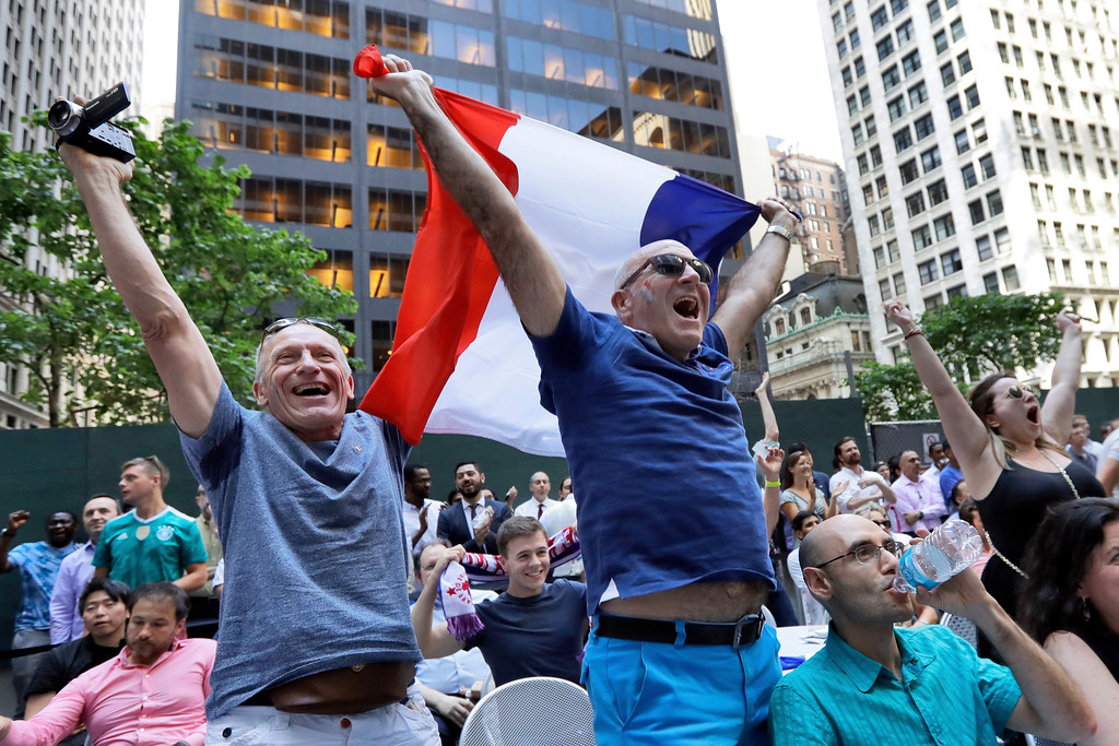 . Arnaod Besselieure, left, from Caen, France, and Regis Bulois, center, from Paris, celebrate France\'s victory at a watch party in New York\'s Financial District, Tuesday, July 10, 2018 for the World Cup semifinal match between France and Belgium. (AP Photo/Richard Drew)