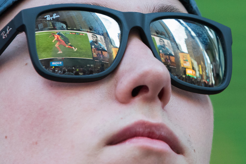 . The World Cup semifinals match between France and Belgium is seen reflected on a fans glasses as he watches the match on a gigantic screen in New York\'s Times Square, Tuesday, July 10, 2018, in New York. (AP Photo/Mary Altaffer)