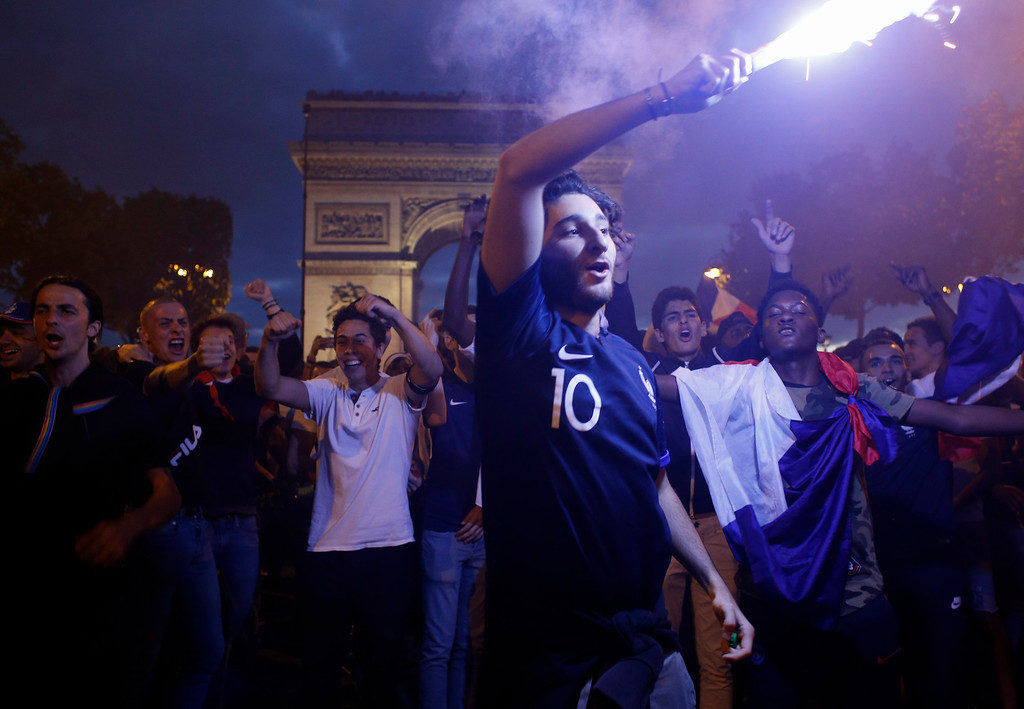 . People celebrate on the Champs Elysees avenue, with the Arc de Triomphe in background, after the semifinal match between France and Belgium at the 2018 soccer World Cup, Tuesday, July 10, 2018 in Paris. France advanced to the World Cup final for the first time since 2006 with a 1-0 win over Belgium on Tuesday. (AP Photo/Thibault Camus)