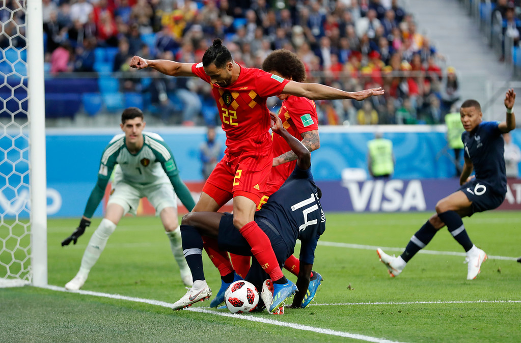 . France\'s Blaise Matuidi, right, challenges for the ball with Belgium\'s Nacer Chadli, center, as Belgium goalkeeper Thibaut Courtois looks them during the semifinal match between France and Belgium at the 2018 soccer World Cup in the St. Petersburg Stadium, in St. Petersburg, Russia, Tuesday, July 10, 2018. (AP Photo/David Vincent)