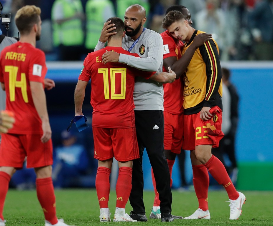 . Belgium assistant coach Thierry Henry consoles Eden Hazard at the end of the semifinal match between France and Belgium at the 2018 soccer World Cup in the St. Petersburg Stadium, in St. Petersburg, Russia, Tuesday, July 10, 2018. France won 1-0. (AP Photo/Petr David Josek)