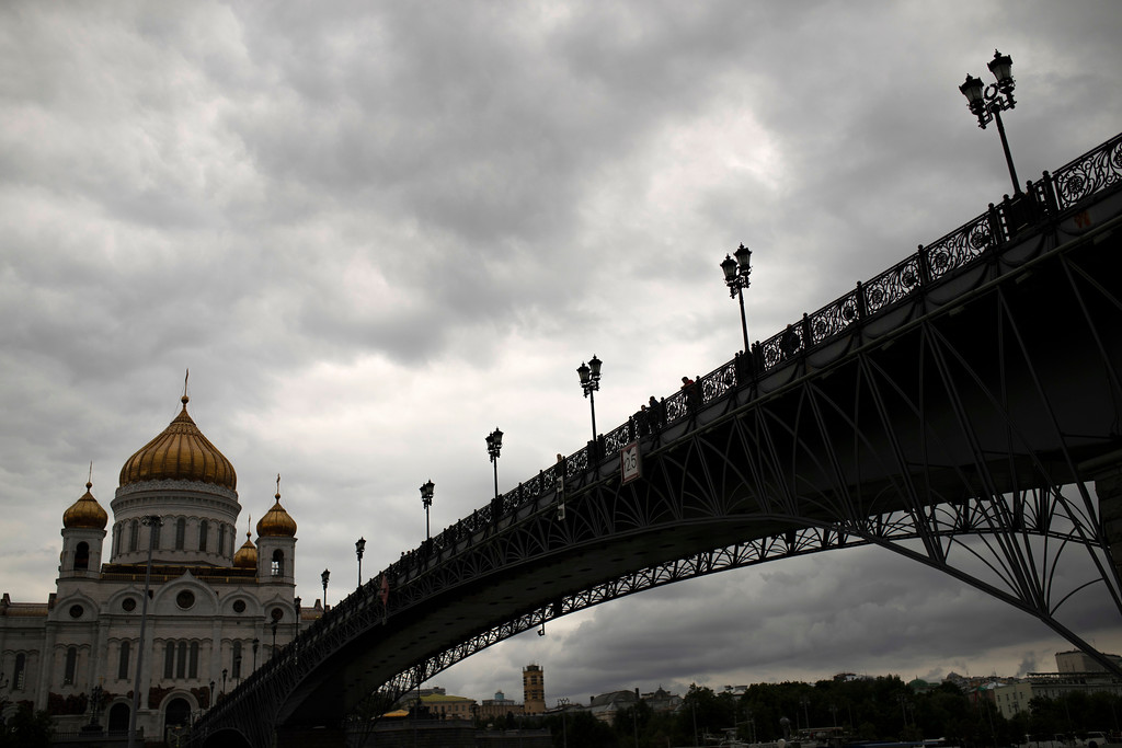 . People walk along the Patriarshy Bridge over the Moskva river next to Christ the Saviour Cathedral at the 2018 soccer World Cup in Moscow, Russia, Tuesday, July 10, 2018. (AP Photo/Francisco Seco)