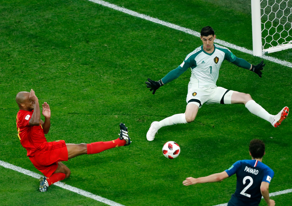 . Belgium goalkeeper Thibaut Courtois, top right, makes a save in front of France\'s Benjamin Pavard, right, during the semifinal match between France and Belgium at the 2018 soccer World Cup in the St. Petersburg Stadium in St. Petersburg, Russia, Tuesday, July 10, 2018. (AP Photo/Pavel Golovkin)