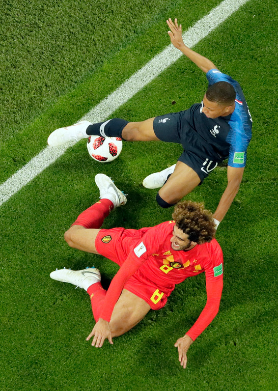 . France\'s Kylian Mbappe, top, is challenged by Belgium\'s Marouane Fellaini during the semifinal match between France and Belgium at the 2018 soccer World Cup in the St. Petersburg Stadium in St. Petersburg, Russia, Tuesday, July 10, 2018. (AP Photo/Dmitri Lovetsky)
