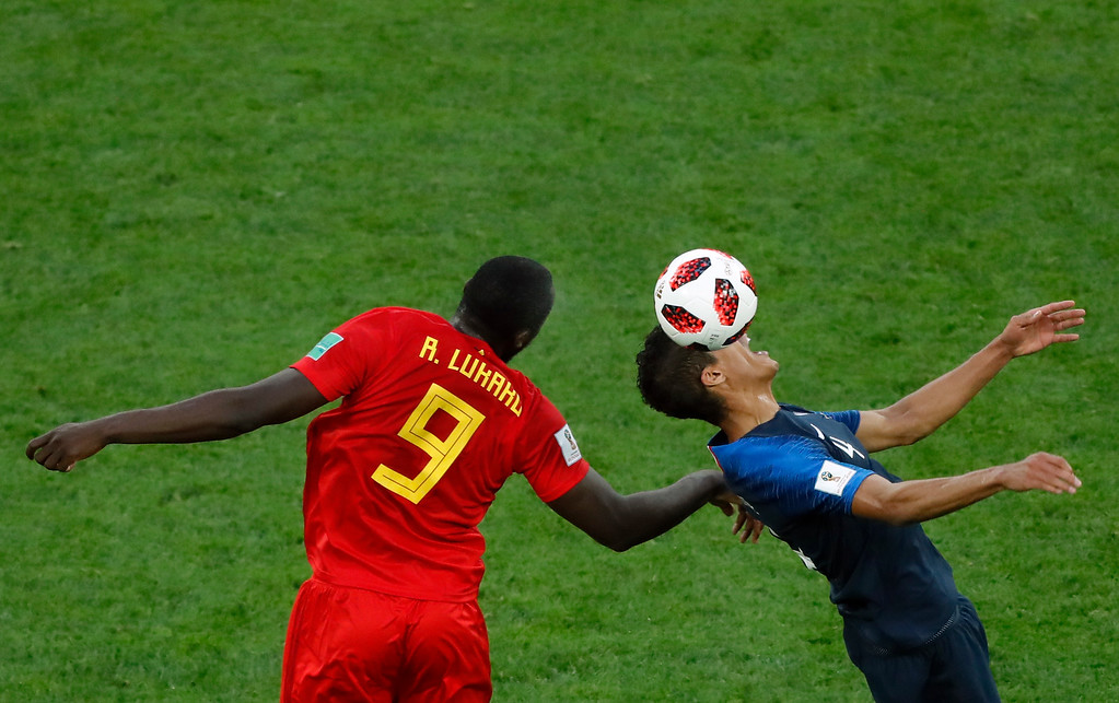 . Belgium\'s Romelu Lukaku, left, jumps for the ball with France\'s Raphael Varane during the semifinal match between France and Belgium at the 2018 soccer World Cup in the St. Petersburg Stadium in St. Petersburg, Russia, Tuesday, July 10, 2018. (AP Photo/Pavel Golovkin)