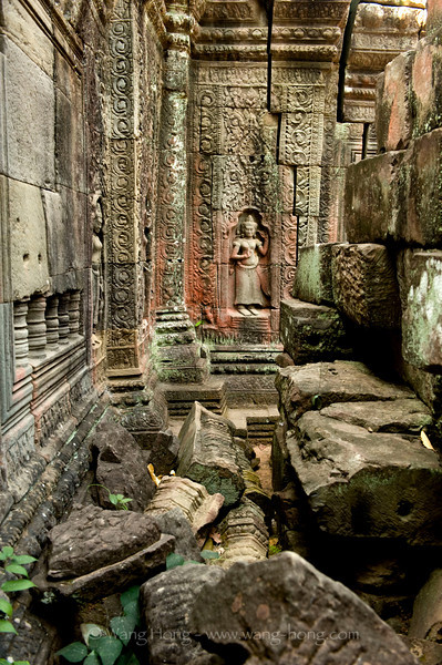 Apsara with peaceful smile and eyes closed amid huge fallen stones, at Banteay Kdei
