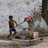 Little one pumping water from a well on the street outside Taj Mahal.
