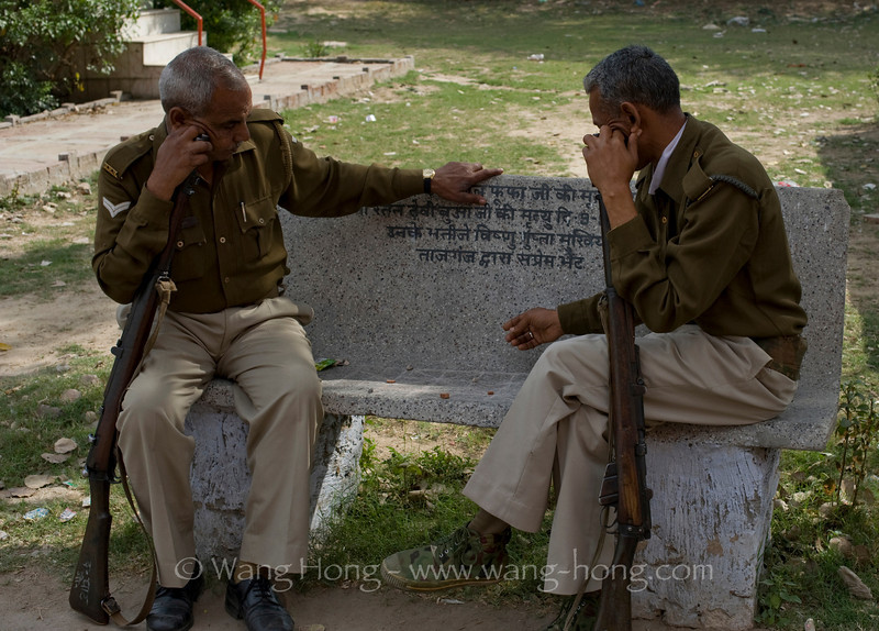 Soldiers playing chess on bench outside Taj Mahal