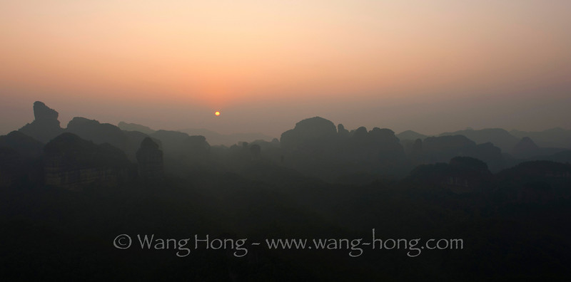 The sun rises over the Danxia landscape in Guangdong, China.