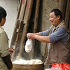 Man selling steamed buns in Xingping, Guangxi Province.