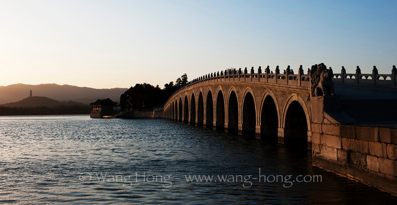 17-arch bridge over Kunming Lake at sunset, Summer Palace. Far in the back the Yuquan Pagada can be seen. 颐和园昆明湖、17孔桥和远处的玉泉山塔