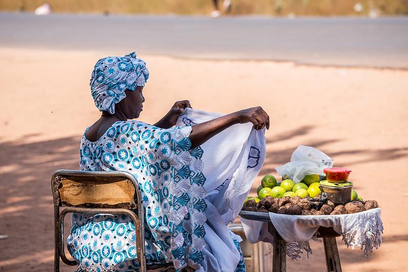 BAKOTEH 2014-01-10<br /> Woman selling fruit on the street just between the huge garbish dump and the SOS children villages in the Gambia, Serrekunda area<br /> Photo Maria Langen / Sverredal & Langen AB