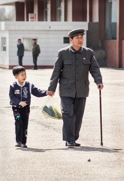 A boy and an old man with a walking stick