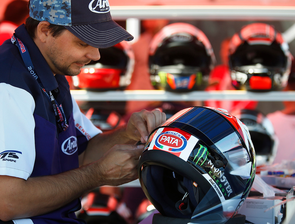 . Arai Helmet technician Jeff Weil replaces the tear off on the shield on the helmet of Kawasaki Racing Team rider Jonathan Rea during the Superbike World Championship at Laguna Seca Raceway in Monterey on Sunday June 24, 2018.   (David Royal/ Herald Correspondent)