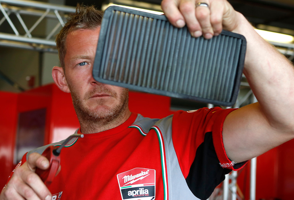 . Lee Mentier cleans the air filter of Milwaukee Aprilla team rider Eugene Laverty\'s motorcycle  during the Superbike World Championship at Laguna Seca Raceway in Monterey on Sunday June 24, 2018.   (David Royal/ Herald Correspondent)