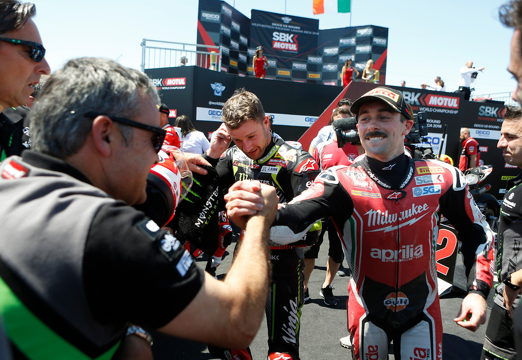 . Milwaukee Aprilla team rider Eugene Laverty of Ireland greets members of Kawasaki Racing Team after placing third in Race 2 of the Superbike World Championship at Laguna Seca Raceway in Monterey on Sunday June 24, 2018. Kawasaki Racing Teams Jonathan Rea at center took the race. (David Royal/ Herald Correspondent)