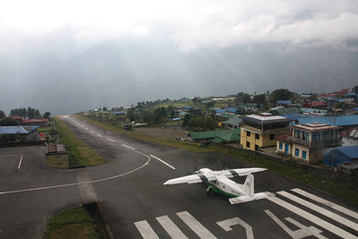 Situated at an elevation of 10,000 feet in the Himalaya Mountains of Nepal, Lukla's airport is undoubtedly the most dangerous in the world. Tenzing-Hillary Airport (VNLK), named after the famous first climbers to summit Mount Everest, features a single 1500 foot runway with a 12% slope gradient. http://en.wikipedia.org/wiki/Tenzing-Hillary_Airport