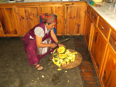 Owner of Lama Lodge & Restaurant cutting squash to feed animals (mules, chickens).