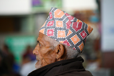This man is wearing a Dhaka topi or Nepali topi, a type of hat, popular in Nepal. The swastika remains widely used in Indian religions, specifically in Hinduism, Buddhism, and Jainism, primarily as a tantric symbol that invokes Lakshmi - the Hindu goddess of wealth, prosperity and auspiciousness.