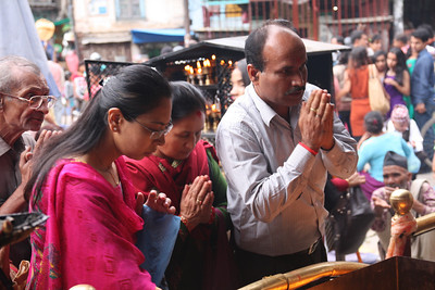 People practicing Hinduism have a tika (or tilaka) on their forehead. http://en.wikipedia.org/wiki/Tilaka