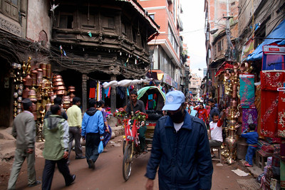 Streets are busy with pedestrians, cars, rickshaws and many speeding mopeds.