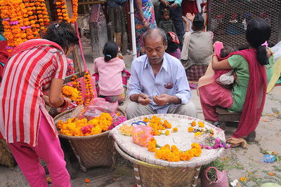 Man making marigold garlands to celebrate Dashain.