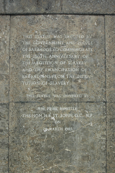 Inscription on the front of the base.  It dedicates the statue on the 150th anniversary of the abolition of slavery in Barbados.